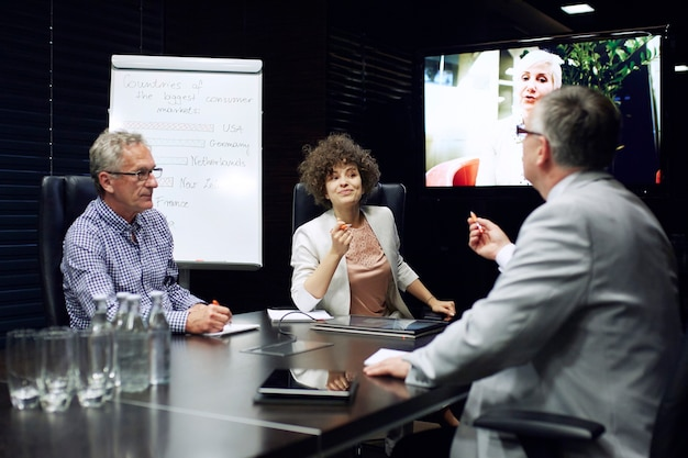 Деловые люди, имеющие видеоконференцию в офисе