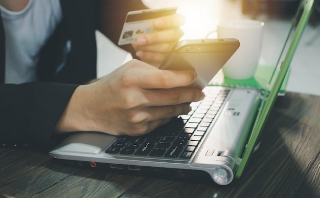 ビジネスマンはクレジットカードを持ってコンピューターを使う
