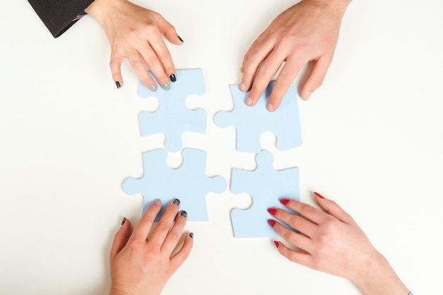 Business people hold in hand a jigsaw puzzle. business solutions, success and strategy concept.