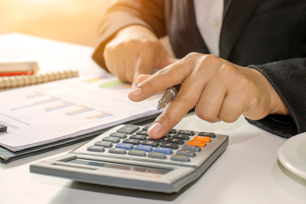 Business people hold pen to press calculator accounting ideas.
