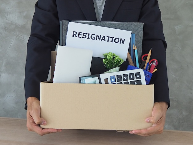 Business people hold personal belongings and resignation letters