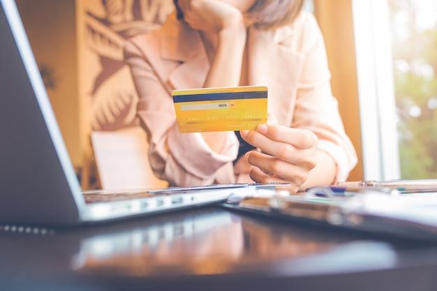 신용 카드를 들고 온라인 쇼핑을 하는 노트북을 사용하는 사업가들.
