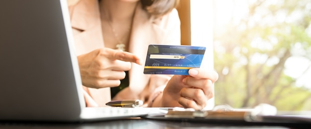Business people holding credit cards and using laptops shopping online.