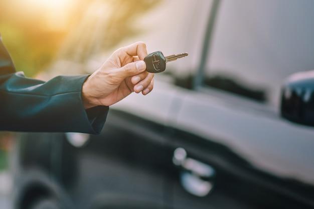 Деловые люди держат ключ на машине