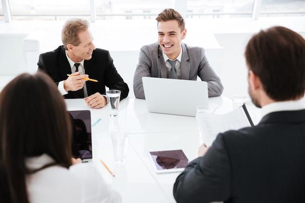 테이블 옆에 앉아 사무실에서 회의하는 동안 회의실에서 비즈니스 사람들