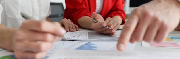 Деловые люди в костюмах обсуждают данные на графах, концепция деловой встречи крупным планом