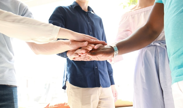 비즈니스 사람들은 회의 중에 함께 손을 맞춥니다.