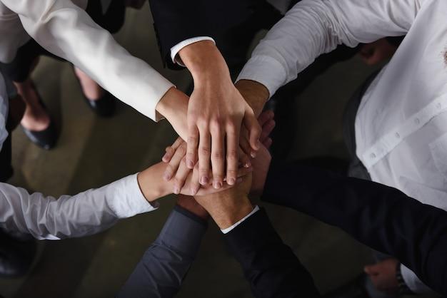 オフィスで輪になって手を組むビジネスマン。チームワークとパートナーシップの概念