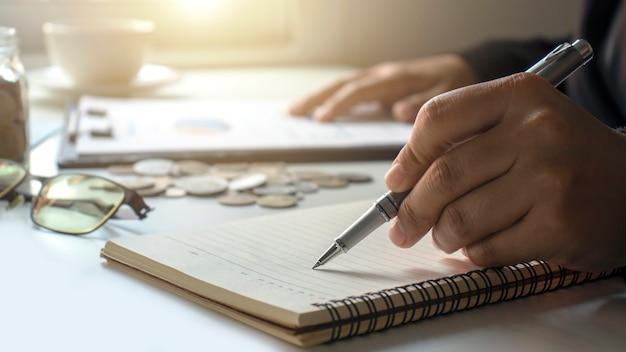 Деловые люди делают записи о доходах и расходах в блокноте для экономии денег на будущее.