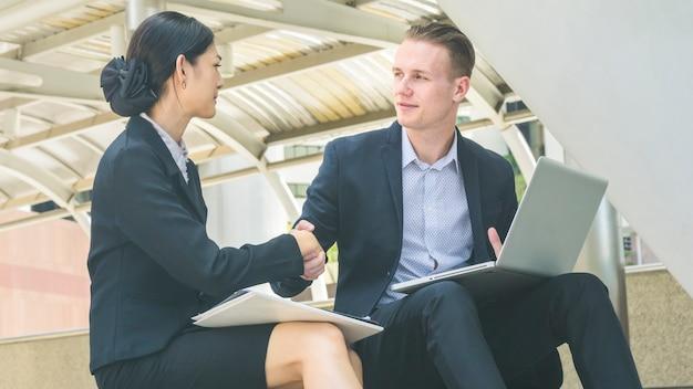 スマートフォンと一杯のコーヒーとラップトップでプレゼンテーションを話し、握手するビジネスマンの女性と白人の賢い男