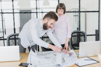 Business people looking at plans in office