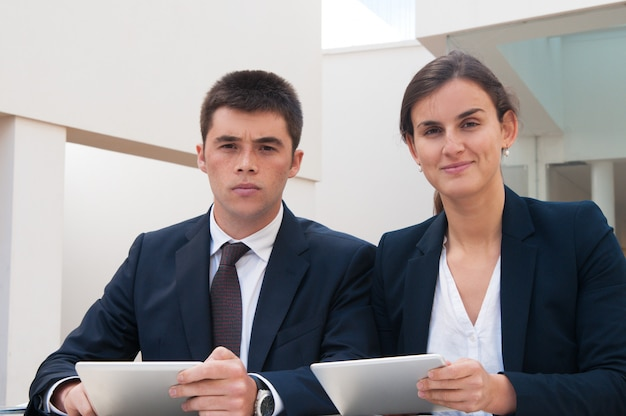 Business people looking at camera and holding tablets at desk