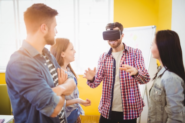 Business people looking at coworker wearing virtual reality headset