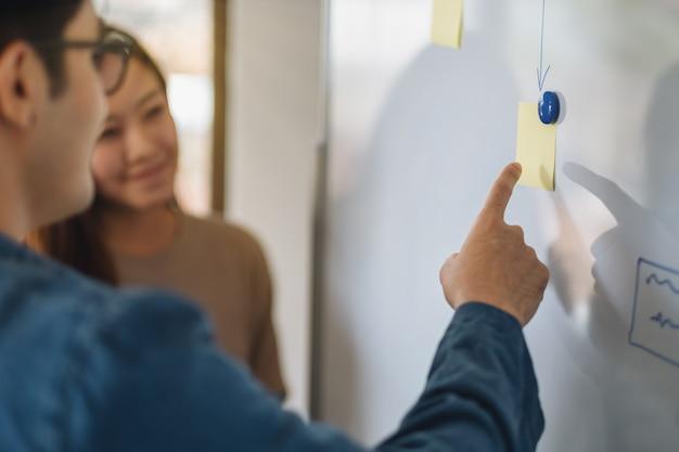 사무실에서 화이트보드를 보고, 토론하고, 가리키는 사업가들