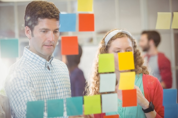 Business people looking at post it on the wall