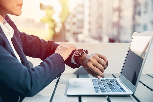 昼休みに腕時計やスマートウォッチを探しているビジネスマンは、ラップトップとのヘルストラッキングの同期を維持します。