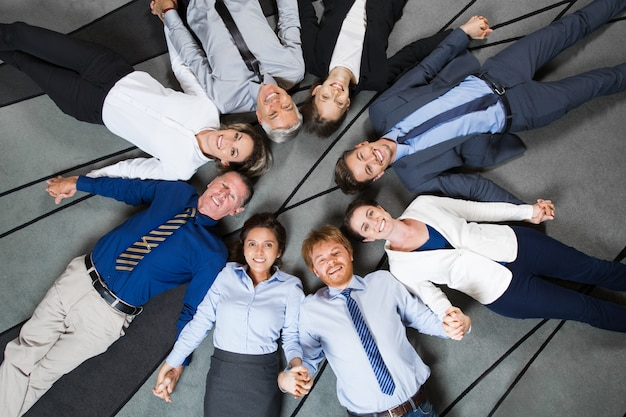 Business people lying on floor and holding hands