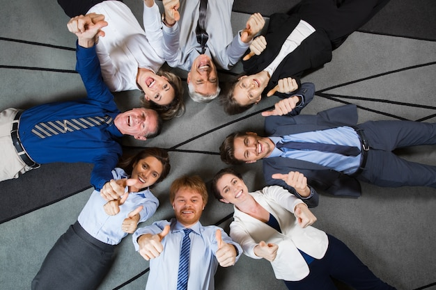 Business people lying on floor showing thumbs up