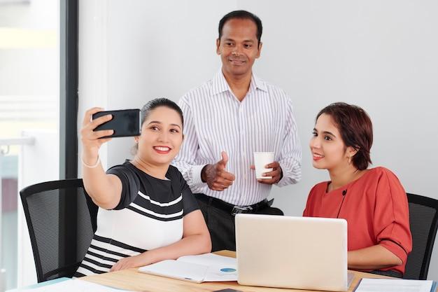 オフィスでselfieの肖像画を作るビジネス人々