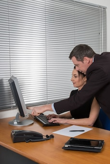 Business people, man and woman meeting and using computer