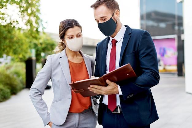 Uomini d'affari in maschere mediche che discutono del piano di lavoro durante la pandemia di coronavirus