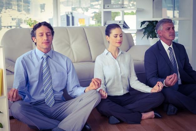 Business people meditating in lotus pose