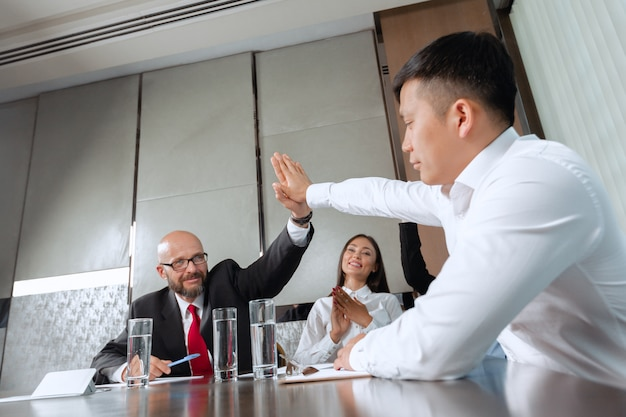 Business people meeting around a boardroom table discussing strategy