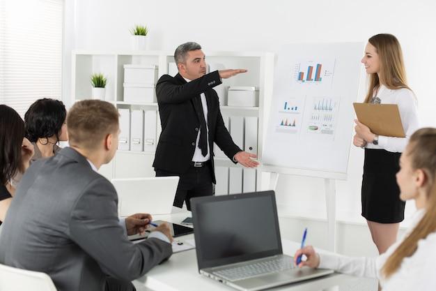 Деловые люди встречаются в офисе для обсуждения проекта. спикер показывает размер прибыли. концепция успеха в бизнесе