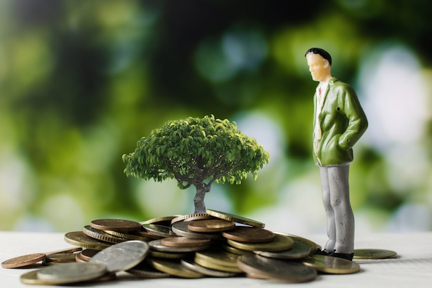 Business people model with money coins with small tree growing