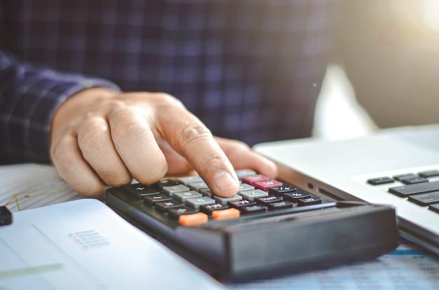 ビジネスマンやビジネスマンは、オフィスのテーブルで電卓やコンピューターを使用します