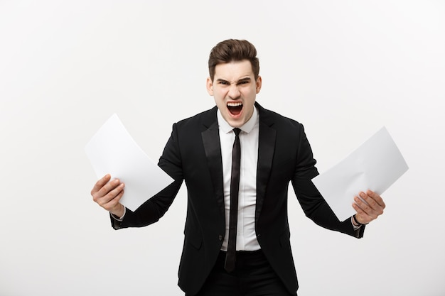Business, people, paperwork and deadline concept - stressed handsome businessman with papers and charts show shocking facial expression with result