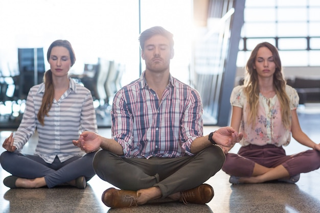 Business people performing yoga on floor