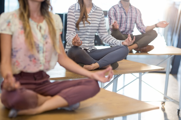 Business people performing yoga on table