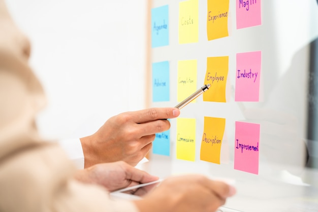 ガラスの壁、戦略分析オフィスコンセプトにアイデアを共有する付箋セッションを配置するスタートアッププロジェクトを計画しているビジネスマン。