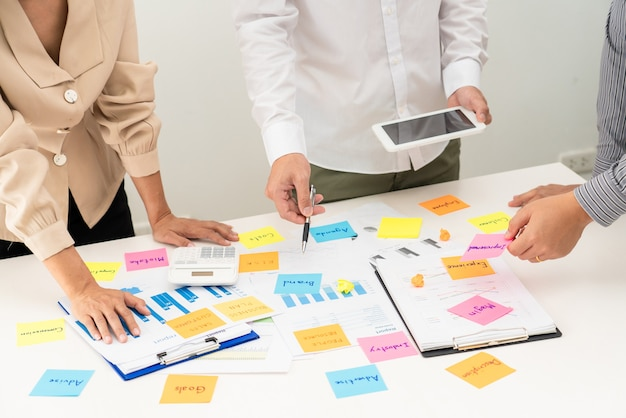 Деловые люди планируют запуск проекта, помещая сеанс стикеров, чтобы поделиться идеей на стеклянной стене, концепции офиса анализа стратегии.