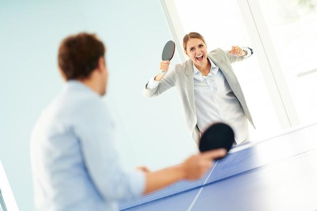Деловые люди играют в настольный теннис в общем офисе