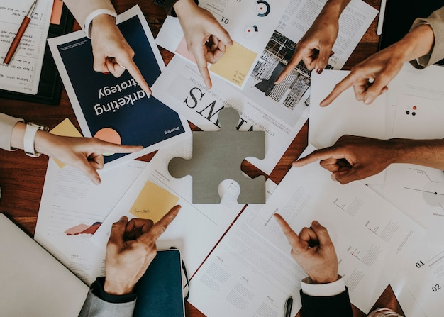 Business people pointing at a puzzle piece