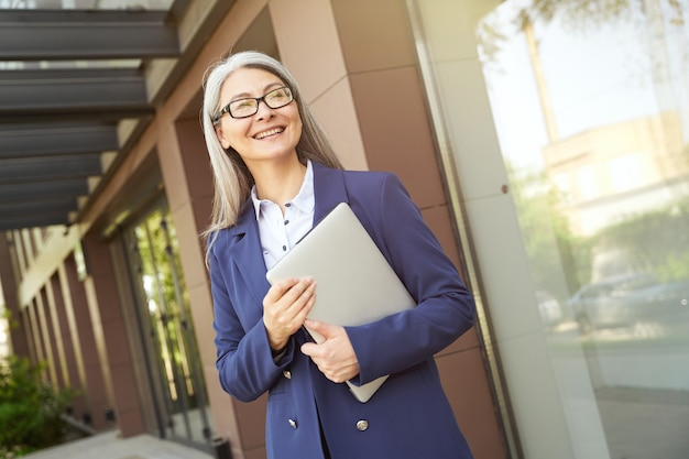 Business people. portrait of a beautiful confident mature business woman wearing classic suit and eyeglasses holding laptop, looking at camera and smiling, standing against office building outdoors
