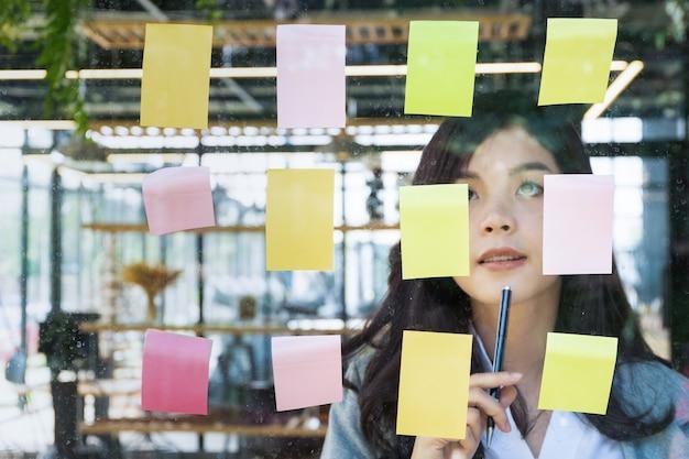 Деловые люди публикуют его заметки идея обсуждения и планирования в стеклянной стене в конференц-зале
