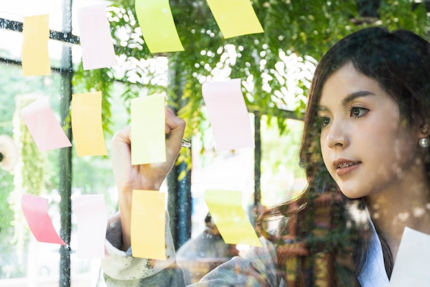 Деловые люди публикуют заметки для обсуждения идеи и планирования в стеклянной стене