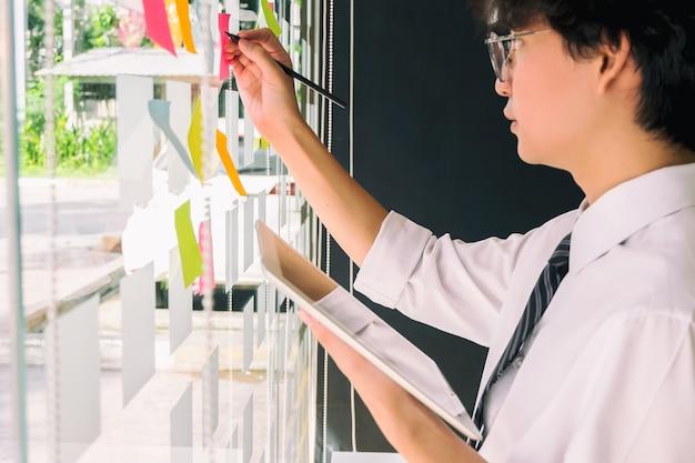 Деловые люди публикуют свои заметки для обмена идеями и планирования в стеклянной стене в конференц-зале