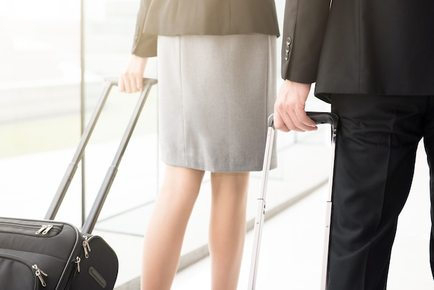 Business people pulling luggage while walking at the airport