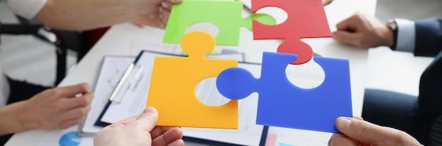 비즈니스 사람들은 비즈니스 개발 개념에 대한 하나의 새로운 아이디어에 여러 가지 빛깔의 퍼즐을 넣었습니다.