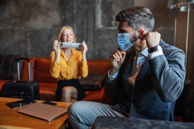 Деловые люди надевают маски во время пандемии короны, сидя в холле отеля перед началом встречи. они в командировке. covid-19 защита