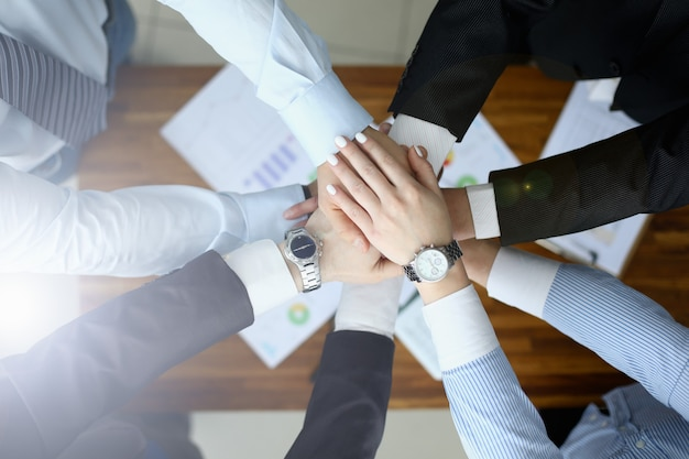 Business people put their hands together over table