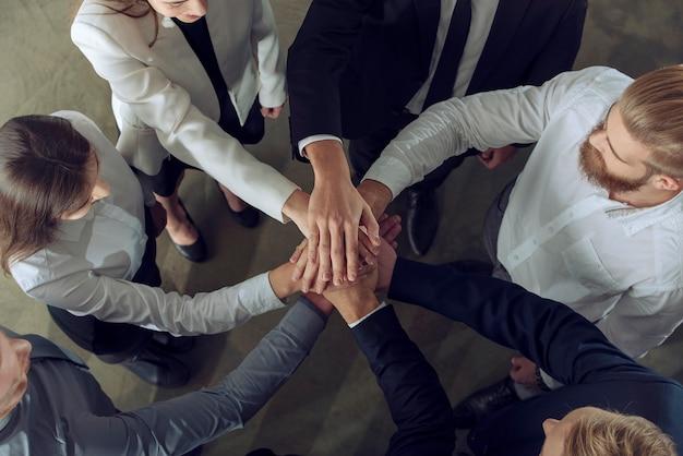 그들의 손을 모으는 사업 사람들. 통합, 팀워크 및 파트너십의 개념.