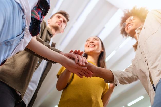 ビジネスの人々が手を合わせます。チームワークとパートナーシップの概念