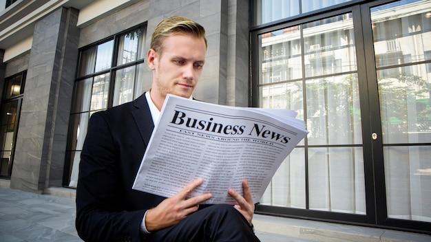 야외에서 비즈니스 신문을 읽는 비즈니스 사람들.