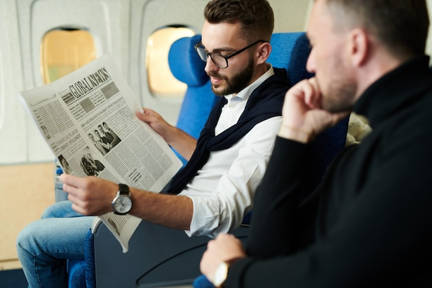 Business people reading newspaper in plane