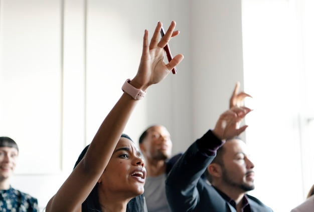 Business people in a seminar raising their hands